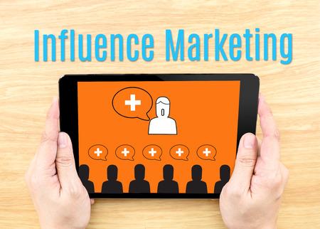 Hand houden van tablet met Influence Marketing woord op houten tafel, Internet business concept