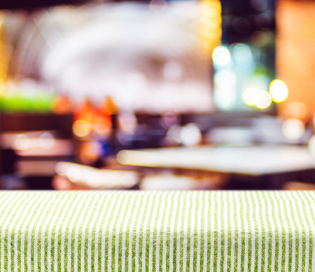 Table with green pattern tablecloth with blur restaurant background,Mock up for display of product.
