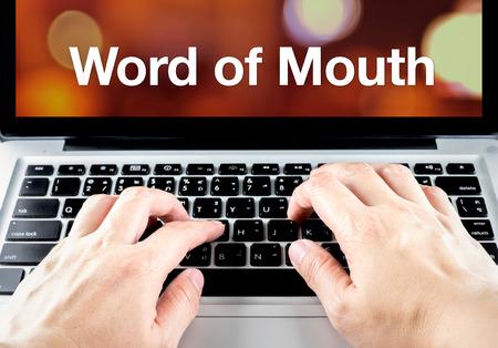 mouth: Palabra de la boca la palabra en la pantalla del port�til con el tipo de mano en el teclado, el concepto de marketing digital.