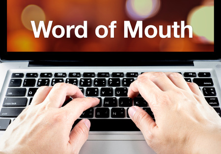 word of mouth: Word of mouth word on notebook screen with hand type on keyboard, Digital marketing concept.