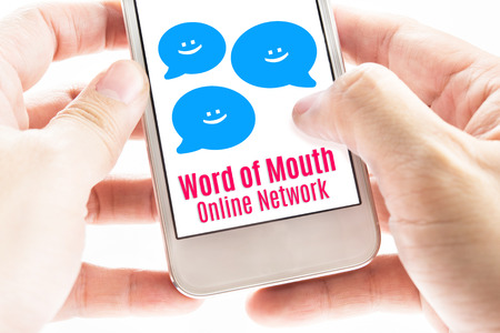 word of mouth: Close up Two hand holding smart phone with word of mouth online network word and icons, Digital concept.