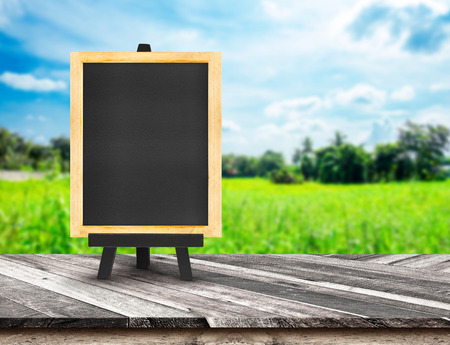 menu land: Menu blackboard on Diagonal Wooden Table top at blurred green field and blue sky,Template mock up for display of your product,Business presentation