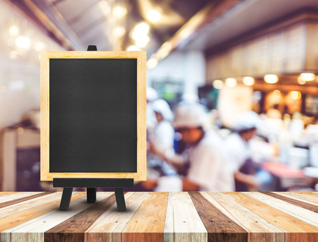restaurant people: Blackboard menu with easel on wooden table with blur open kitchen at  restaurant background, Copy space for adding your content. Stock Photo