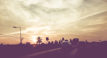 exotic car: Vintage filtered : silhouette landscape of cars on road,sunset scene in Thailand.