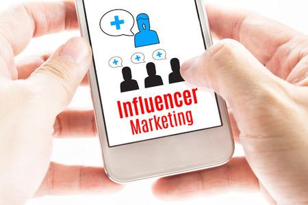 Close-up Twee hand houden van slimme telefoon met beïnvloeder Marketing woord en iconen, digitale concept. Stockfoto