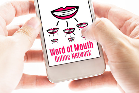 influencer: Close up Two hand holding smart phone with word of mouth online network word and icons, Digital concept.