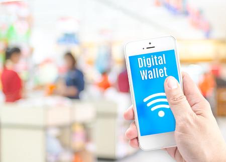 pagando: Mano que sostiene teléfono móvil con el monedero digital en el supermercado desenfoque de fondo, el concepto de la economía digital. Foto de archivo