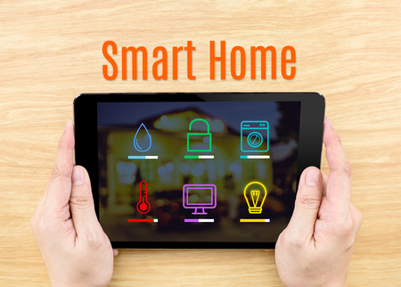 Finger click screen with Smart home application interface with keyboard on wooden table,Internet Business concept Banque d'images