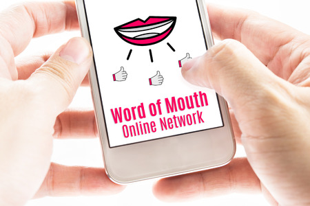 communication tools: Close up Two hand holding smart phone with word of mouth online network word and icons, Digital concept.