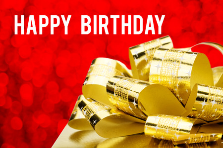 birthday greetings: Close up Golden present  with big bow and Happy Birthday word at red bokeh blur background. Stock Photo