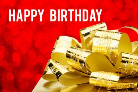 Close up Presente de oro con el arco grande y feliz cumpleaños palabra en fondo rojo blur. Foto de archivo - 42662386