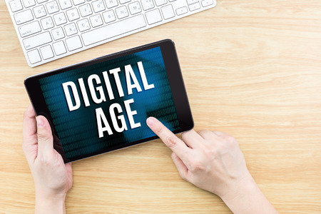 age: Finger click screen with Digital age word with keyboard on wooden table,Digital Technology concept. Stock Photo