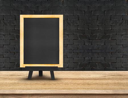 pizarron: Menú de la pizarra en la tapa de tabla de madera en la pared de ladrillo negro, Plantilla maqueta para la exhibición de su producto, la presentación de negocios. Foto de archivo