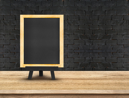 blackboard: Menu blackboard on  Wooden Table top at black brick wall,Template mock up for display of your product,Business presentation. Stock Photo
