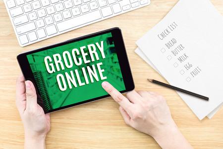 abarrotes: Dedo de la pantalla, haga clic con textos en l�nea de comestibles con el teclado sobre la mesa de madera, el concepto de marketing digital.