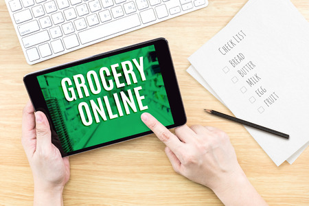 grocery baskets: Finger click screen with Grocery online word with keyboard on wooden table,Digital Marketing concept. Stock Photo