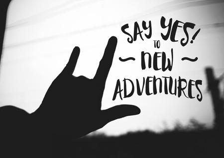 """inspiración: Cita de la inspiración: """"Diga sí a nuevas aventuras"""" en la silueta de la mano el amor signo en la carretera, tipográfico motivación. Foto de archivo"""