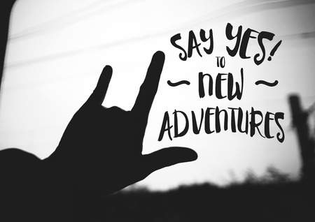 say: Inspiration quote : Say yes to new adventures on silhouette Hand love sign on road ,Motivational typographic. Stock Photo