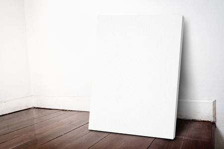 Blank white canvas frame leaning at house wall and dark brown parquet floor, Mock up for adding your design. Stock Photo