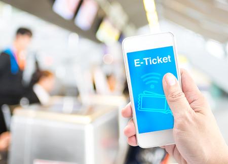 手ぼかし空港チェックインの背景、概念のデジタル予約と E チケットと携帯電話を保持しています。