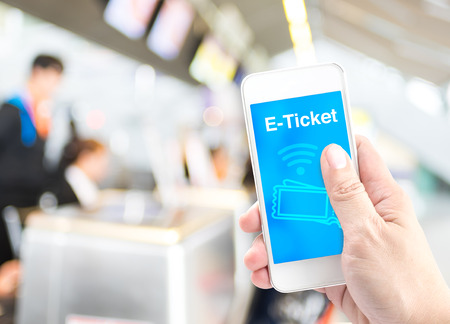 Hand holding mobile with E-Ticket with blur airport check-in background, Digital Booking concept.