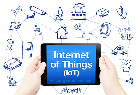 Hand hold tablet with Internet of things (IoT) word on screen with doodle icon on white background.