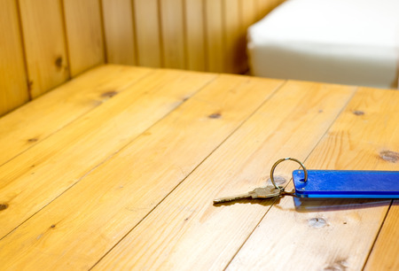 hotel suite: Keychain on wooden table in hotel,leave space for adding your text