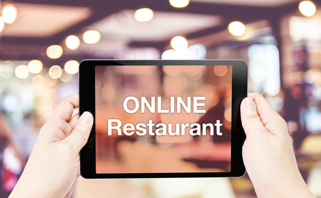 Hand hold tablet with Online restaurant word on screen with blur restaurant background. Stock Photo