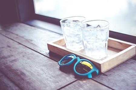 vasos de agua: Filtro de la vendimia, gafas de sol y el vaso de agua fría en la bandeja de madera en la ventana del restaurante.