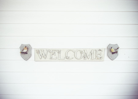 welcom: Welcom sign on wood plank wall. Stock Photo