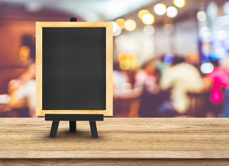 Blackboard menu with easel on wooden table with blur restaurant background, Copy space for adding your content.