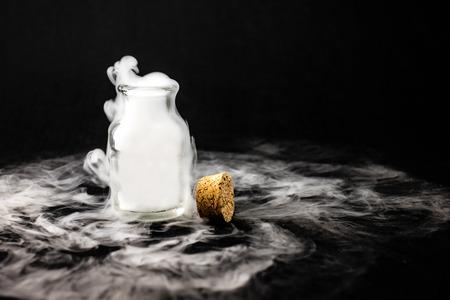 in the smoke: Humo blanco en el interior de la botella de cristal en el fondo negro, concepto Mistery Halloween.