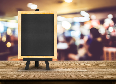 table of contents: Blackboard menu with easel on wooden table with blur restaurant background, Copy space for adding your content.