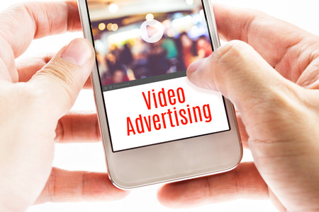 Close up Two hand holding mobile with Video Advertising word, Digital business concept.