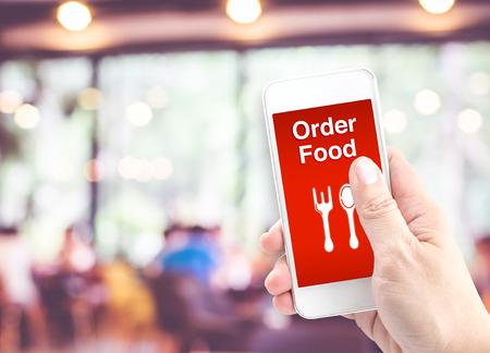 food: Mão segurando móvel com alimentos Ordem com borrão restaurante, Ordem onine alimento conceito. Banco de Imagens