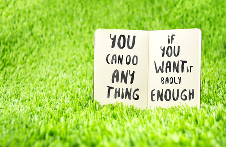 motivation: Inspiration quote :  You can do anything if you want it badly enough on notebook on grass ,Motivational typographic. Stock Photo