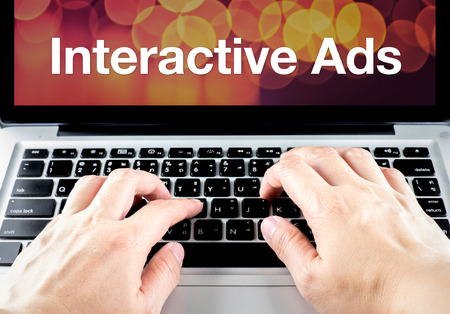 video marketing: Interactive ads word on laptop screen with hand type on keyboard, Digital Advertising concept.
