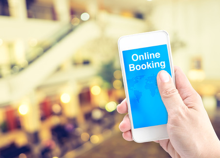 Hand holding mobile with online booking with blur background, Digital Booking concept.