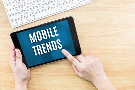 business trends: Touch on screen with Mobile Trends word with keyboard and notebook on wooden table,Digital business concept.