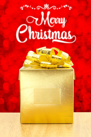christmas present: Merry Christmas with Golden Present box on wood table at red bokeh light background, Holiday concept.