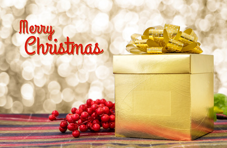 christmas present: Merry Christmas word with Gold present box and ribbon on table with sparkling gold bokeh light background, Holiday concept. Stock Photo