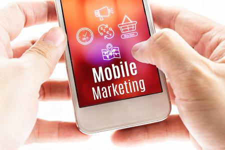 모바일 마케팅 단어와 아이콘, 디지털 개념 스마트 폰을 들고 두 손을 닫습니다. 스톡 콘텐츠