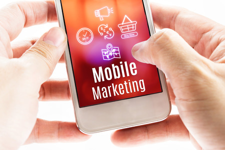 mail marketing: Close up Two hand holding smart phone with Mobile Marketing word and icons, Digital concept. Stock Photo