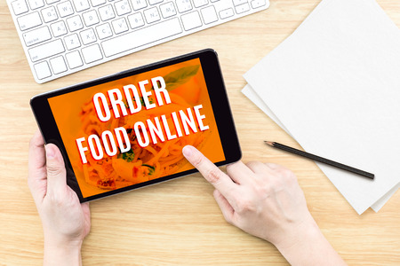 klawiatury: Palec kliknięcie ekranu z jedzeniem zamówieniu online słowa z klawiatury na drewnianym stole, jedzenie projektowania koncepcji.