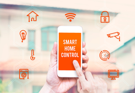 home security system: Hand holding smart phone with home control application with blur home background, Smart home concept.
