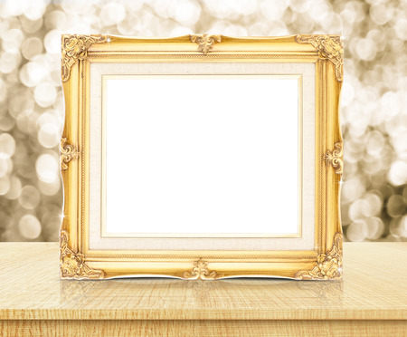 Blank golden vintage photo frame with sparkling gold bokeh wall and wooden table.