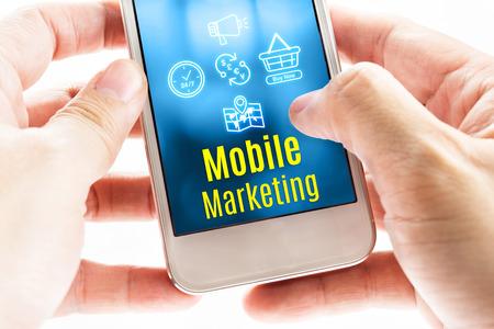 redes de mercadeo: Cierre de dos manos sosteniendo tel�fono inteligente con la palabra y los iconos de Mobile Marketing, concepto digital.