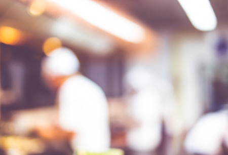 Blurred background : Groups of Chef cooking in the open kitchen,customer can see they cooking at food counter, cooking chef with light bokeh.