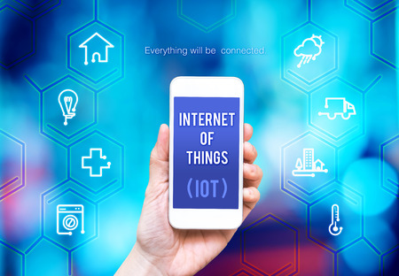 internet concept: Hand holding smart phone with Internet of things (IoT) word and object icon and blue blur background, Digital business concept..