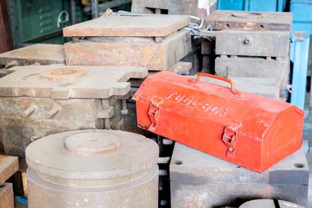 lunares rojos: grunge caja de herramientas de metal rojo en los moles rústicos en fábrica.